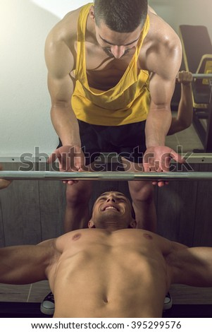 A handsome young muscular sports man doing weight lifting and gets help from his friend who is personal trainer.