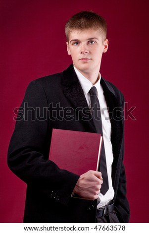 A handsome young student with book in the hand on a dark red background - stock photo