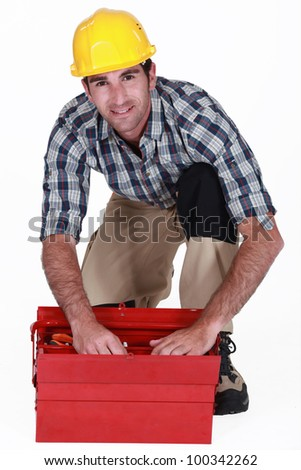 A handyman looking through his toolbox. - stock photo