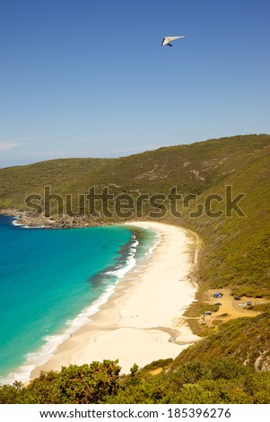 A hang glider flies over Shelley Beach in West Cape Howe National Park, near the towns of  Albany and Denmark in Western Australia. - stock photo