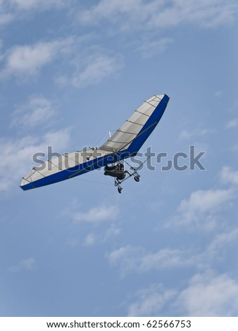 A hang glider is gliding towards the photographer against a beautiful cloudscape