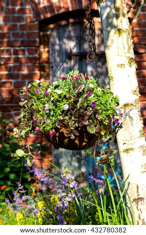 A hanging flower basket in the garden, a great way for garden landscaping. - stock photo