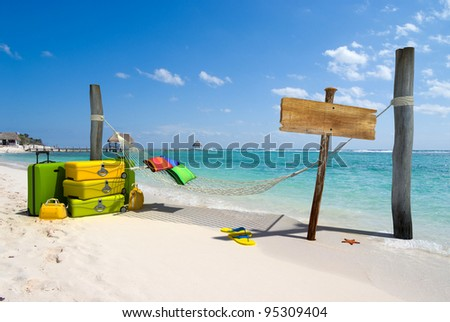 A hanging hammock, a wooden sign post , a pile of luggage, thongs and starfish on a beach resort - stock photo