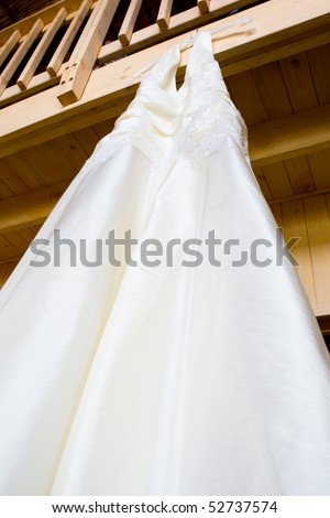 A hanging wedding dress photographed from below