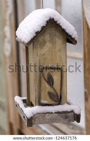 A hanging wooden birdfeeder sits empty beneath a mantle of winter snow.