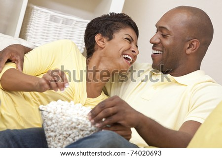 A happy African American man and woman couple in their thirties sitting at home laughing, eating popcorn and watching a movie together