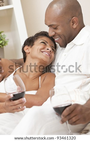 A happy African American man and woman couple in their thirties sitting at home together smiling and drinking glasses of red wine. - stock photo