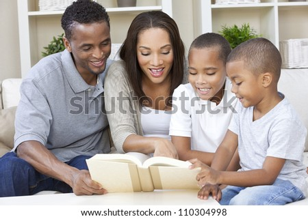A happy African American man, woman and boys, father, mother and two sons, family sitting together at home reading a book