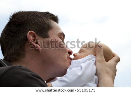 a happy and proud young father kissing his 7 weeks old daughter