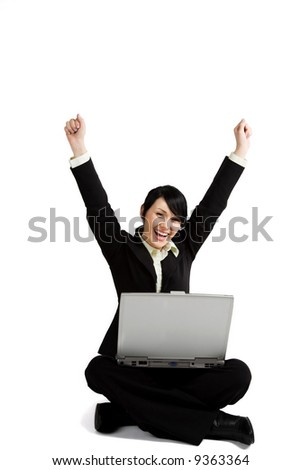 A happy and successfull businesswoman with her arms raised working with a laptop - stock photo
