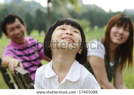 A happy Asian family at a park - stock photo