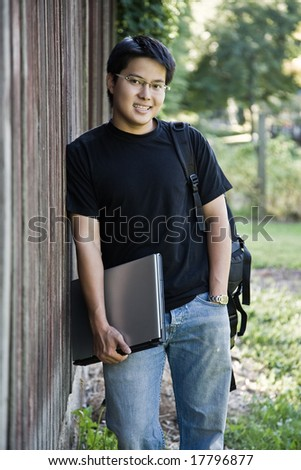 A happy asian student carrying a laptop and a backpack