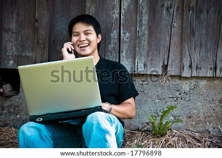 A happy asian student talking on the phone while working on his laptop