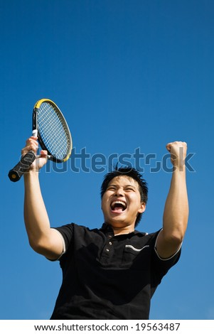 A happy asian tennis player in joy of winning - stock photo