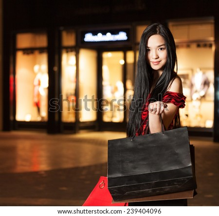A happy asian woman shopping with shopping center background - stock photo