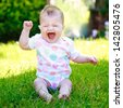 A happy baby in a vest sitting on the grass in the garden, screaming - stock photo