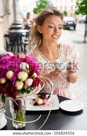A happy beautiful young girl are drinking tea. Outdoors - stock photo