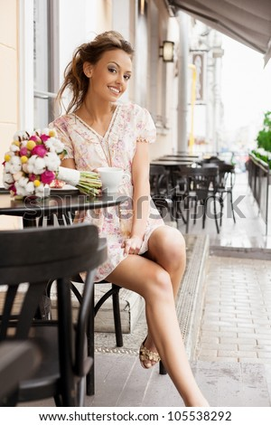 A happy beautiful young woman are drinking tea. Outdoors - stock photo