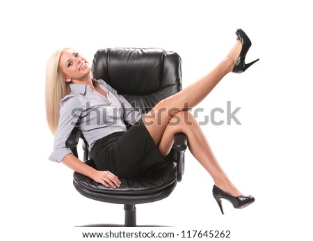 A happy business woman sitting in a swivel chair with her legs up in the air isolated on white. - stock photo