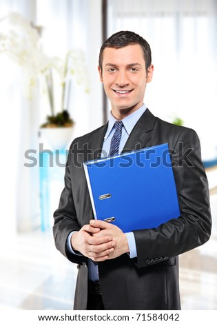 A happy businessman with blue folder posing in the office - stock photo