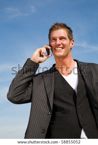 A happy caucasian businessman talking on the phone outdoor