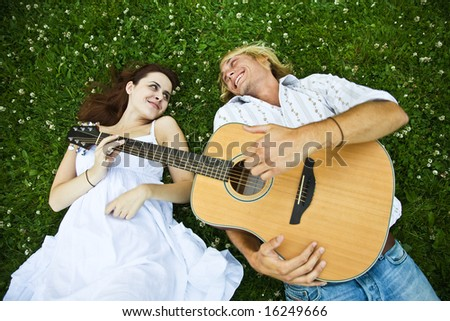 A happy caucasian couple playing guitar at a park