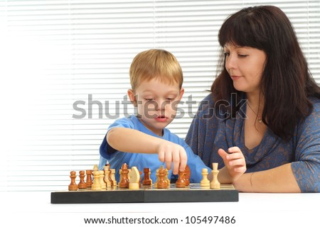 A happy Caucasian mother and son playing chess against a light background