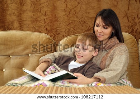 A happy Caucasian mother with her son sitting on the couch on a light background