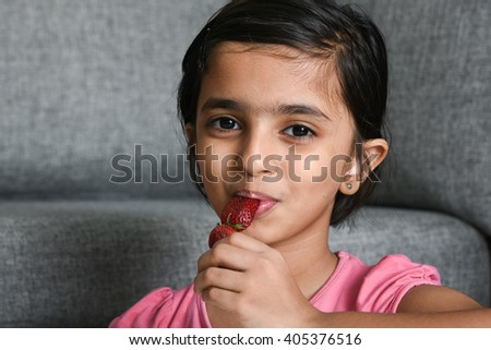 A happy, cheerful, laughing child/ kid/ young girl licking, enjoying her tasty sweet lollipop on summer vacation/ holiday Kerala, India, Asia. Indian daughter playful looking at ice cream and smiling. - stock photo