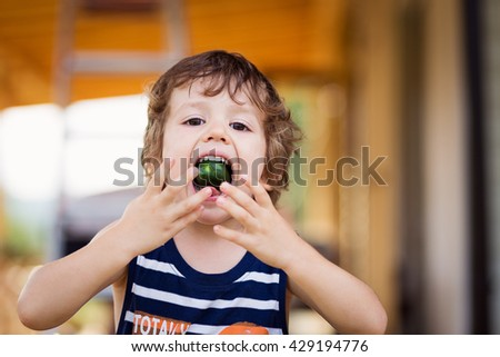 A happy child eating a cucumber. Kids eat vegetables outdoors. Healthy snack for children.  - stock photo