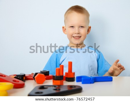 A happy child playing with toy instruments - stock photo