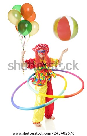 A happy clown in wild patterns and colors twirling 2 hula hoops while holding a balloon bouquet and bouncing a beach ball in the air.  Motion blur on hoops, ball and left hand.  On a white background. - stock photo