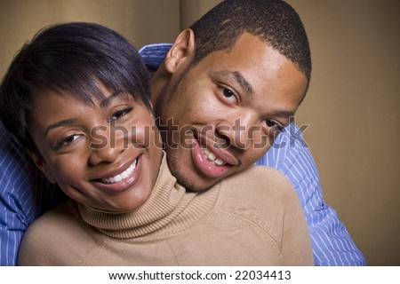 A happy couple embraces each other in front of a neutral background in landscape format - stock photo