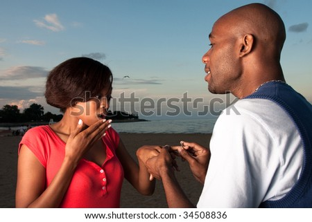 a happy couple gets engaged on a beach - stock photo