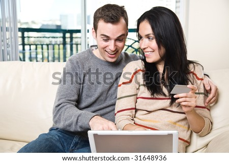 A happy couple holding a credit card shopping online from home