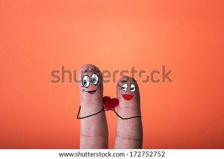 A happy couple in love with painted smiley and hugging. - stock photo
