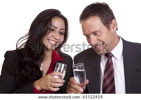 A happy couple in their business clothing drinking to success. - stock photo