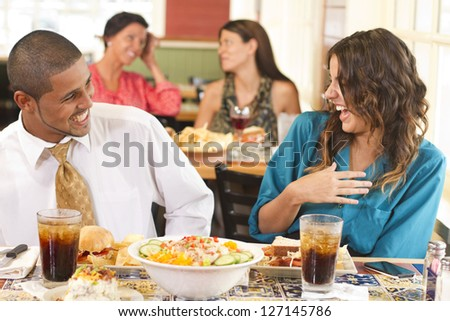 A happy couple laughing at lunch in a restaurant. - stock photo