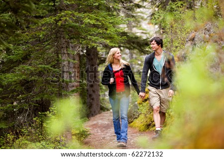 A happy couple looking at eachother and walking in the forest holding hands - stock photo