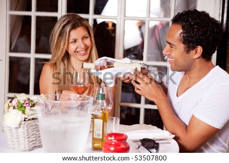 A happy couple on a date to an outdoor cafe; shallow DOF with focus on male - stock photo