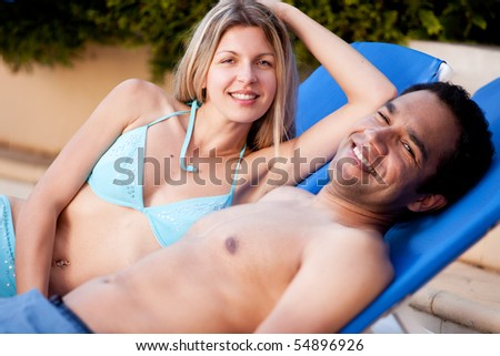 A happy couple on beach chairs, looking at the camera - stock photo