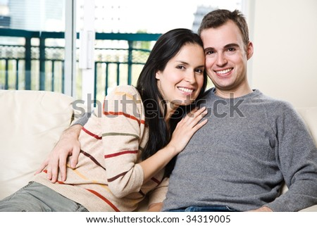 A happy couple sitting on the couch and relaxing at home - stock photo