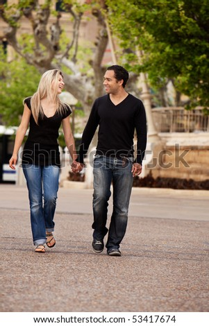A happy couple walking in the city looking at each other