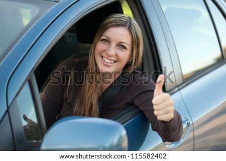 A happy driver leaning out of the window and showing thumbs up - stock photo
