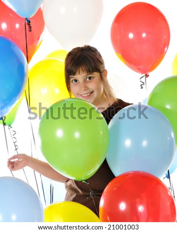 A happy elementary girl surrounded by helium balloons.