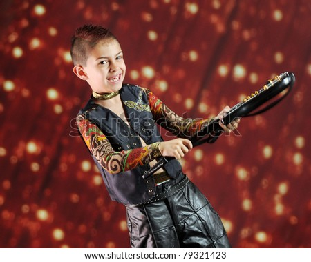"""A happy elementary """"rock star""""  wielding his guitar before a light-studded curtain.  Motion blur on hands and guitar. - stock photo"""