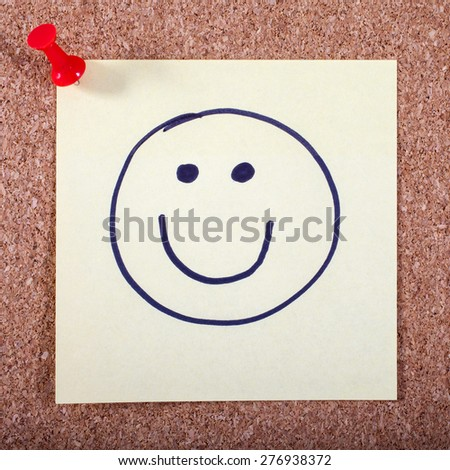 A Happy Face on a Memo Page pinned to a Noticeboard. - stock photo