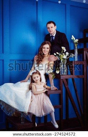 A happy family concept. Cute little girl and cheerful father who is tenderly holding his beautiful pregnant wife in wedding dress are sitting on a ladder a blue wall background. - stock photo
