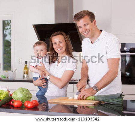 A happy family cutting vegetables in a kitchen, looking at the camera