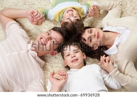 A happy family holding on carpet with clutched hands - stock photo